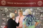 Dr. Carolyn Gunning, former Dean visits with alumni in front of one of the historical displays.